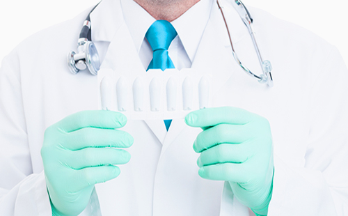Hands of doctor in gloves holding medical candles